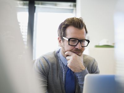 Focused businessman working at laptop hand on chin