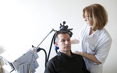Hospital, pain centre. France. An rTMS session (repetitive transcranial magnetic stimulation) carried out by a nurse.
