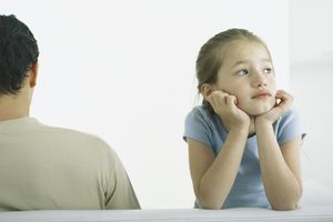 Girl holding head, leaning on elbows next to man, rear view