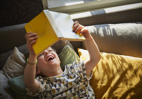 Boy lying down reading book laughing