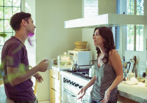 Male and female white couple in a kitchen appearing to have a disagreement