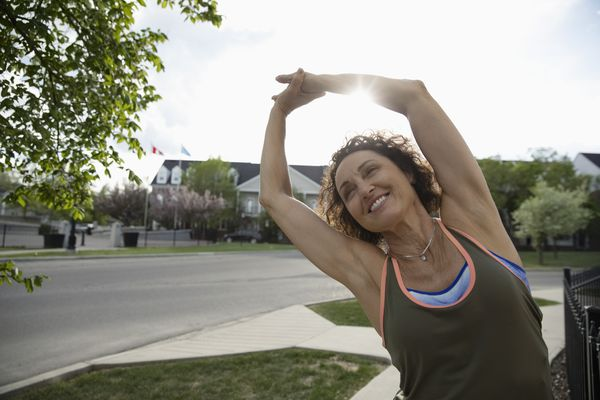 Smiling senior female runner stretching arms on sunny neighborhood sidewalk