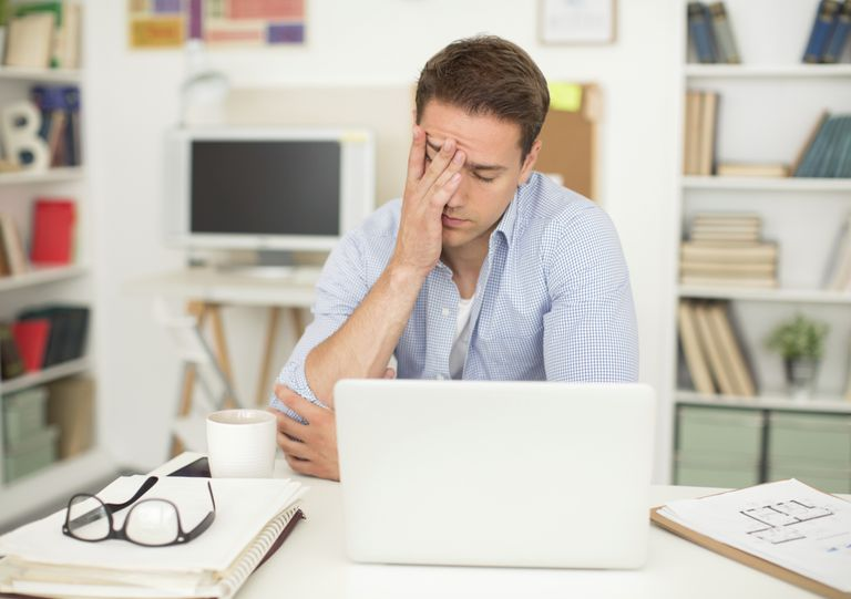 Man working on laptop, rubbing forehead
