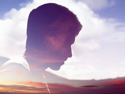Male face silhouetted in sky as if a hallucination