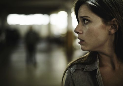 Fearful woman looking over shoulder