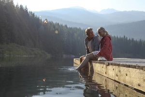 Older couple sitting on a wooden dock at a lake.