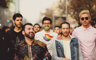 Five men of different nationalities at a pride parade