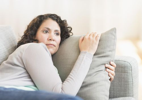 worried woman on sofa