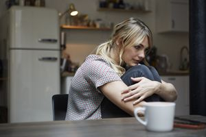 sad woman hugging her knees while sitting in a chair at her kitchen table