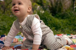Baby crawling on a blanket outside
