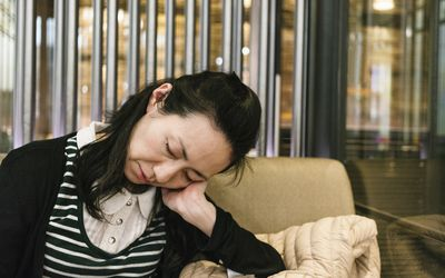 tired woman taking a nap in a cafe
