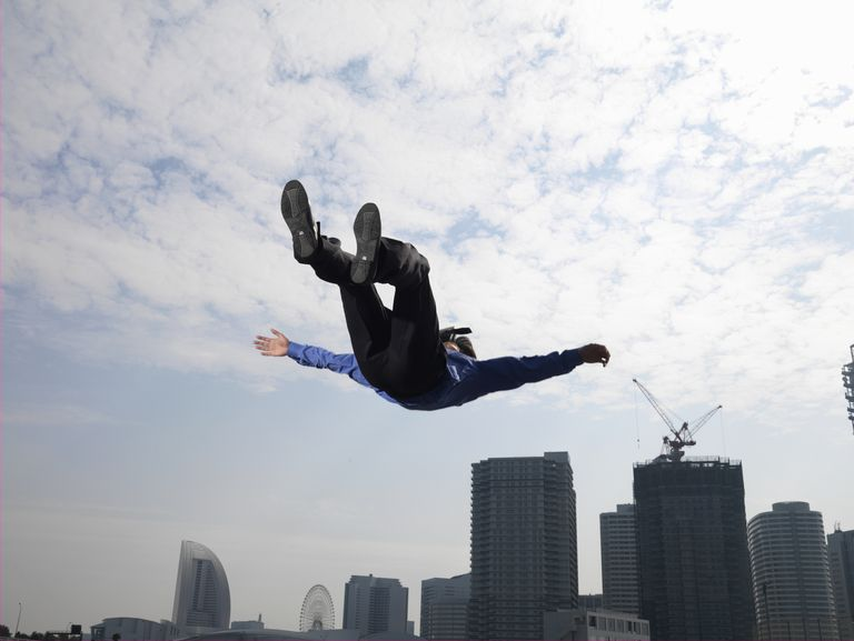 Businessman jumping in air, skyscrapers in background, low angle view