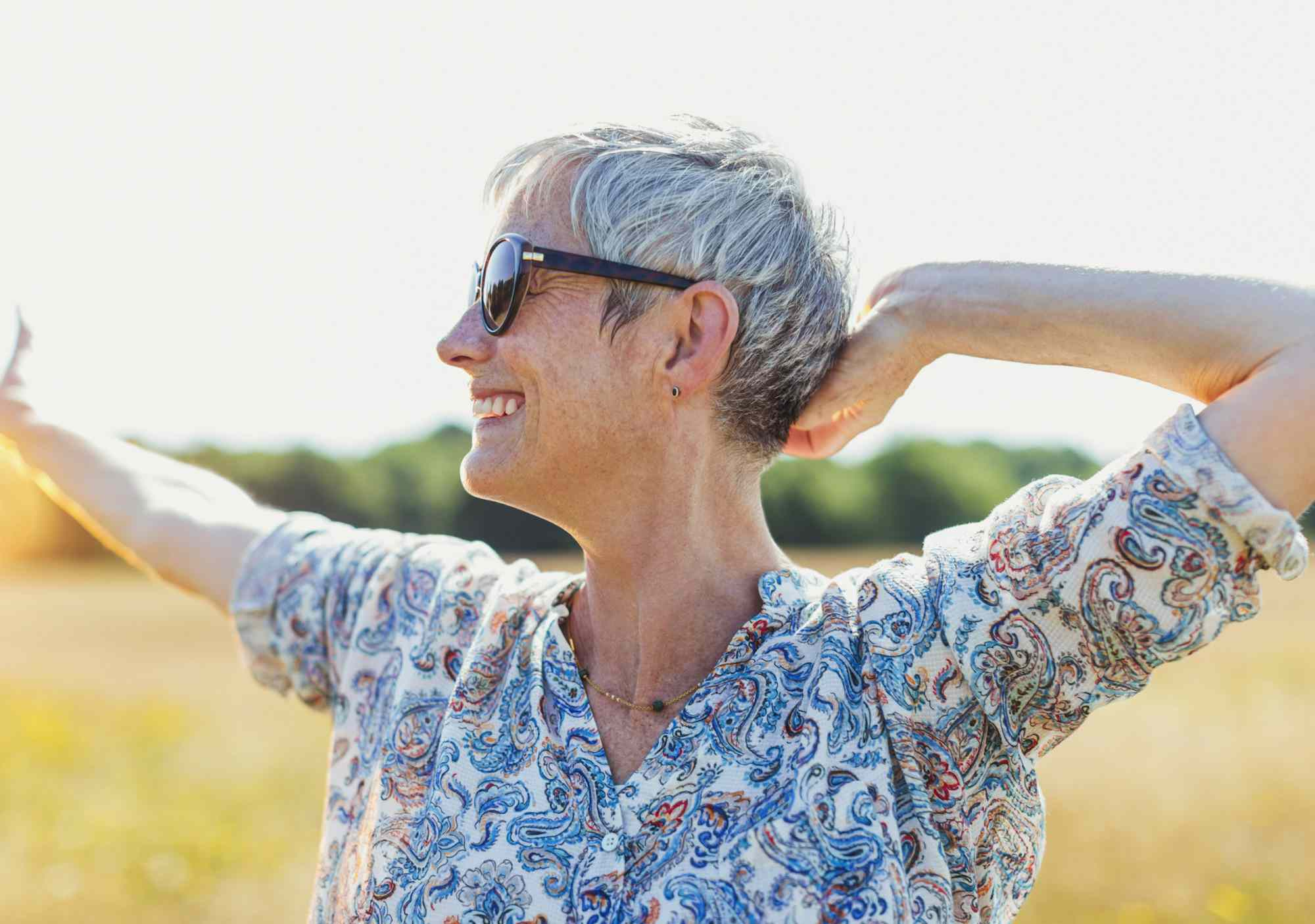 Enthusiastic senior woman with arms outstretched in sunny field