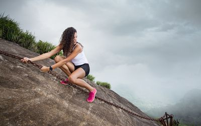 Young woman climbing on rock formation