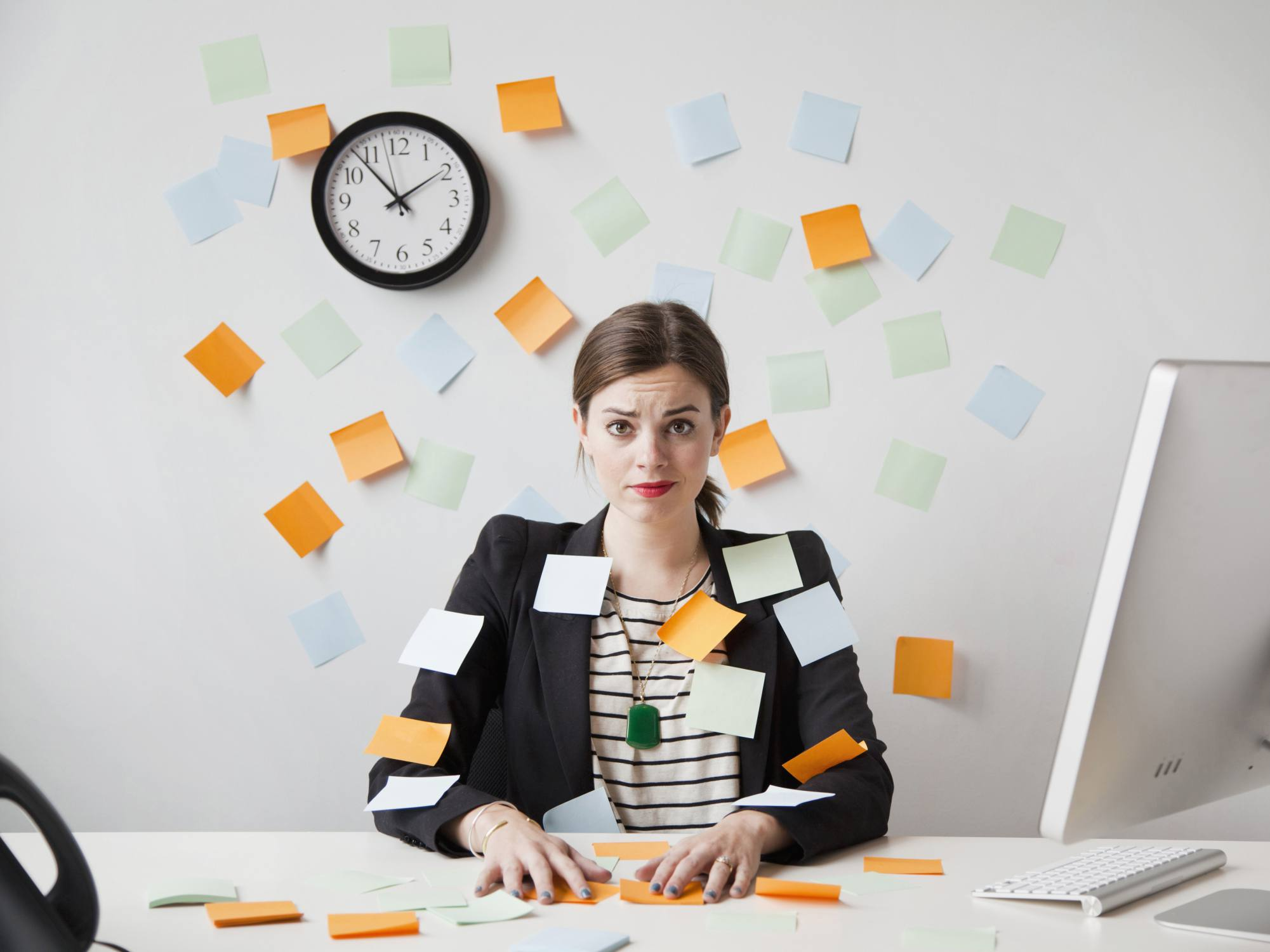 Stressed woman with sticky notes all over her and her office