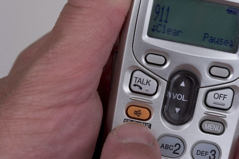 man's hand dialing 911 on telephone