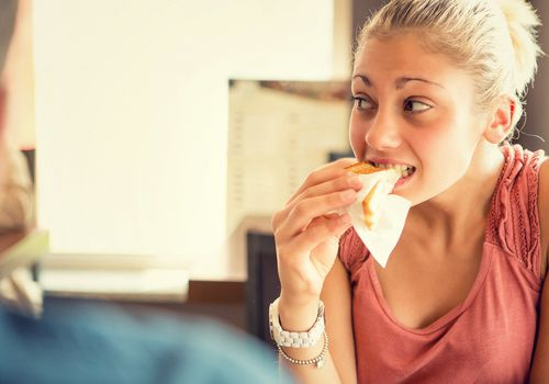 Young woman eat a toast at italian café