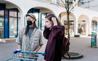 queer couple outside wearing masks
