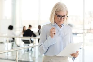 Anxious woman reading notes outside an office full of people
