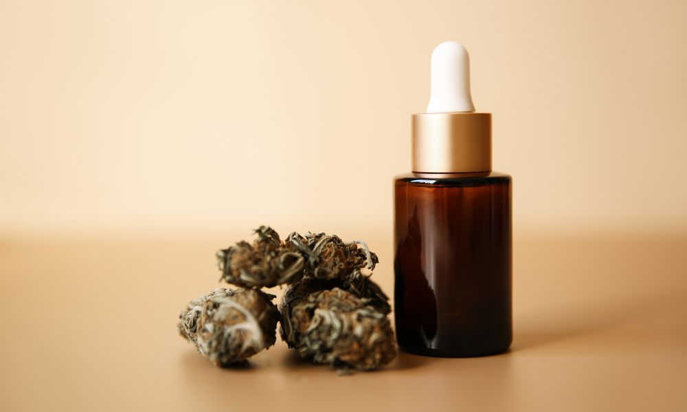 CBD oil bottle next to marijuana flower on a beige background