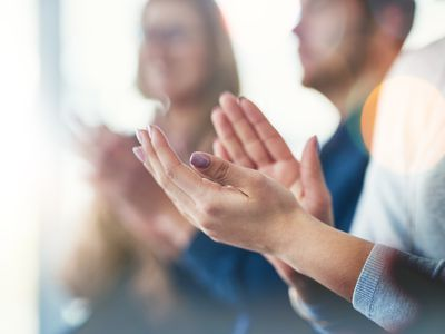 Cropped shot of a group of businesspeople clapping hands while sitting in a meeting