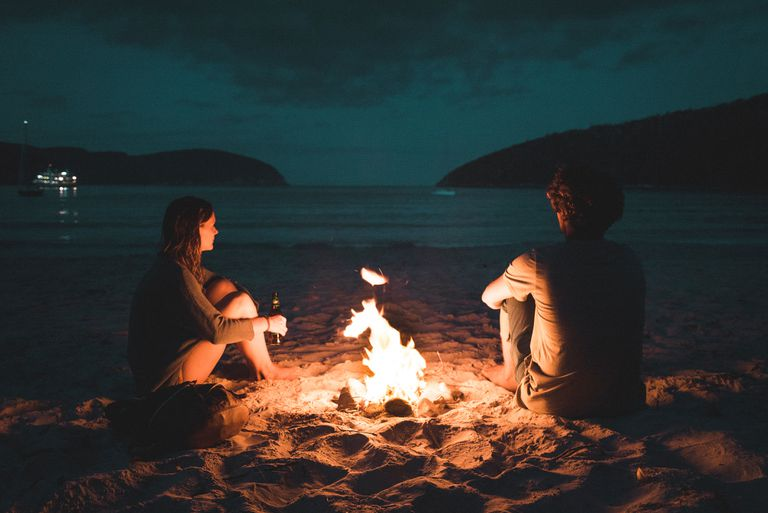 man and woman sitting by a campfire on a beach at night