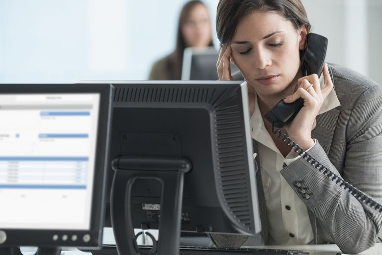 Caucasian businesswoman talking on telephone at desk
