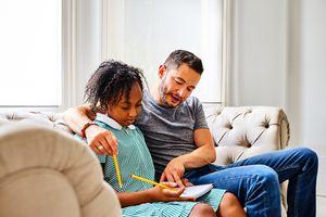 Transgender man with daughter explaining how to do homework