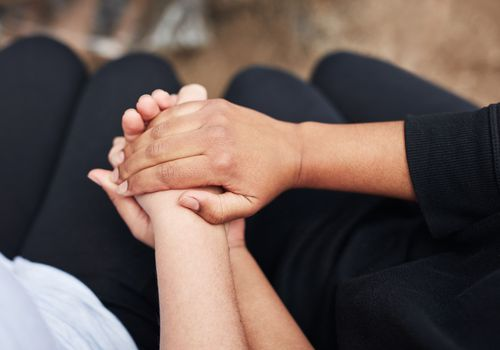 image of two hands holding each other, one black person, one white.