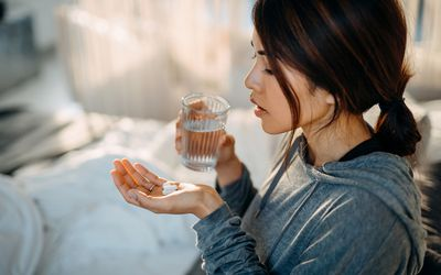Young Asian woman sitting on bed and feeling sick, taking medicines in hand with a glass of water - stock photo