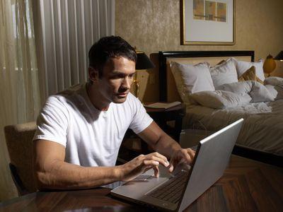 Man using laptop in bedroom
