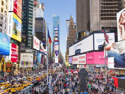 Skyscrapers, billboards, and crowds with busy traffic and yellow cabs in Times Square
