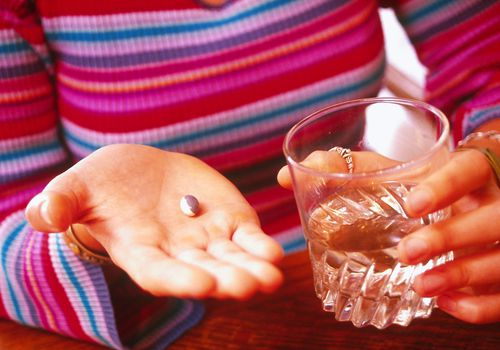 Woman holding pill and water