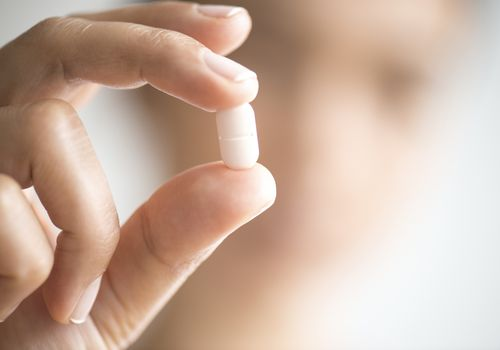 A woman's fingers holding a white pill