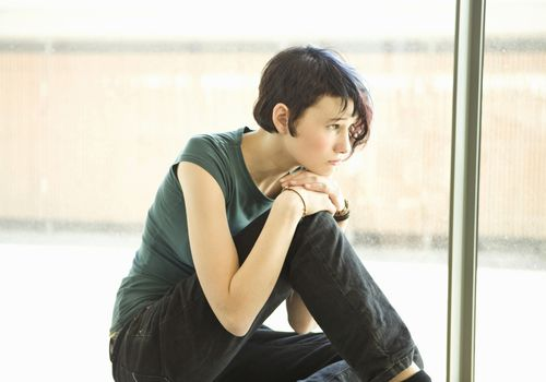 Sad teenage girl sitting alone in front of window