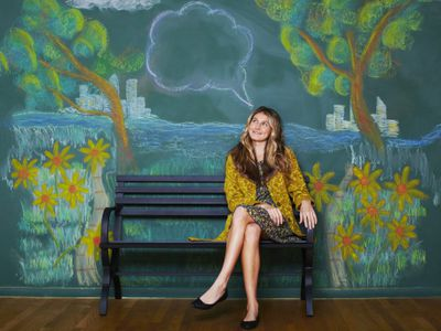 Woman sitting on a bench in front of chalk mural