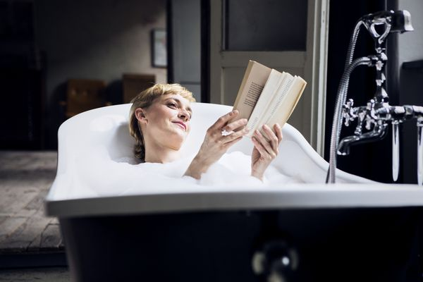 Woman reading in the bath