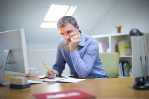 upset man writing in journal at desk in front of computer