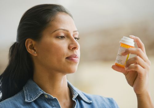 Woman reading the label on a medication bottle