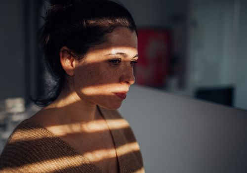 Portrait of a sad young woman in her apartment, with a sun on her face, that is breaking through the window blinds