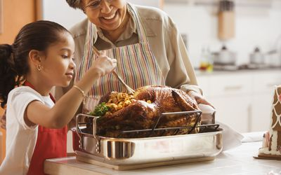 Grandmother and grand daughter cooking a stuffed turkey