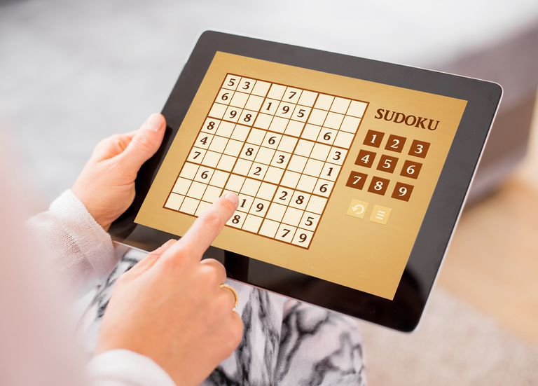 Woman playing Sudoku on tablet computer