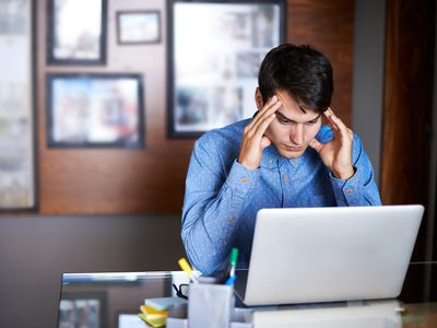 stressed man with fingers on temples using laptop