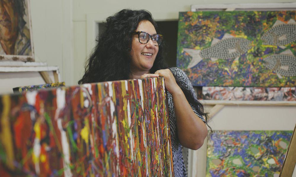 An Indigenous woman smiling in an art studio.