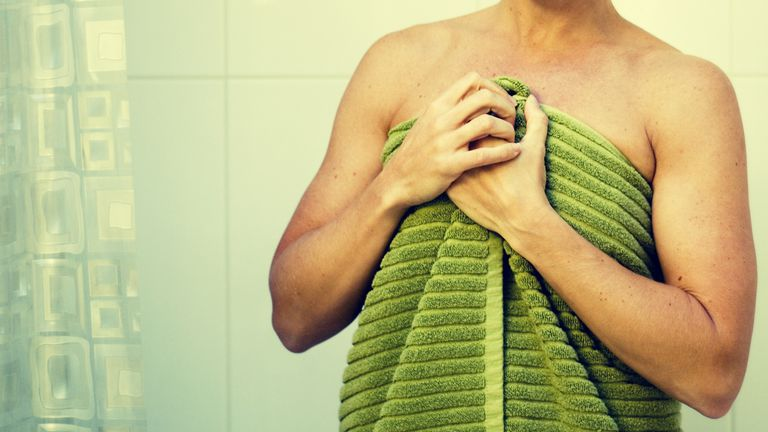 woman standing outside shower with towel on