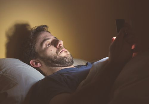 A white man with facial hair lies in bed looking at his smart phone screen.