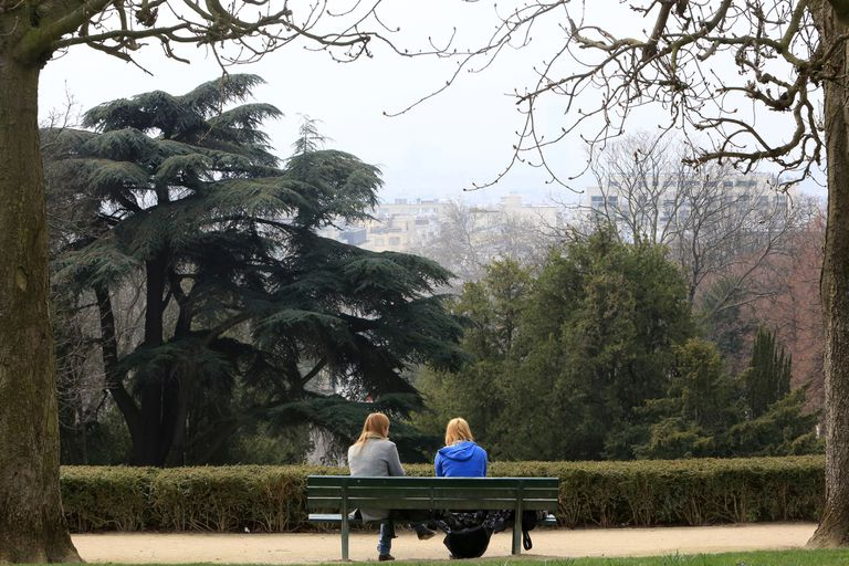 Two women sitting on a park bench.
