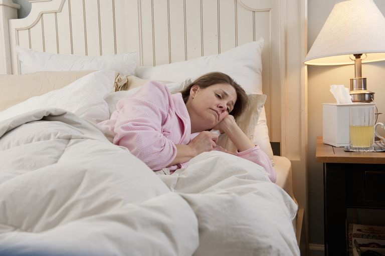 A woman laying in bed with the flu