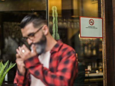 Man smoking outside bar with smoking ban