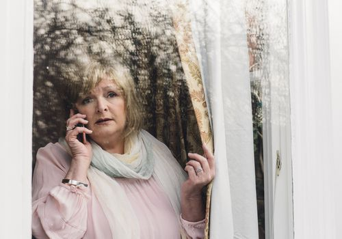 Elderly woman looking out window on cell phone